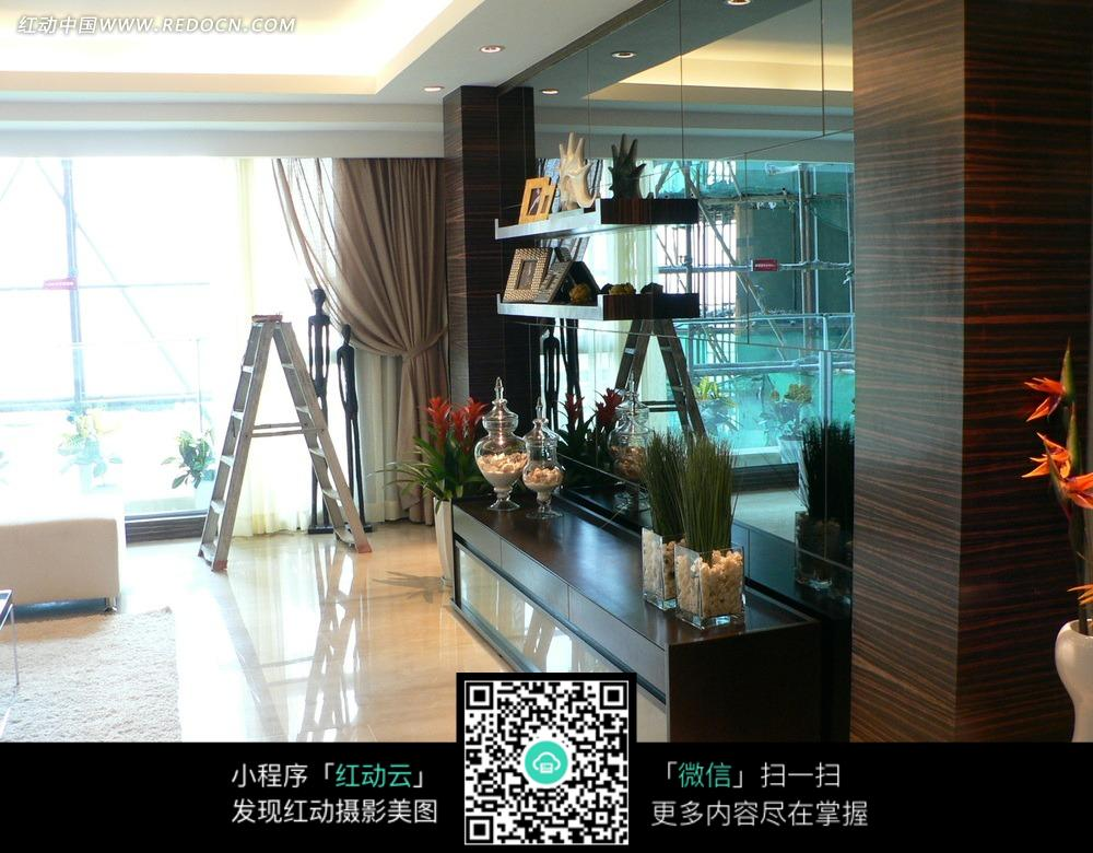 环境居住 室内设计 > 玻璃光亮墙壁前的黑色柜子和柜子上的精美装饰品