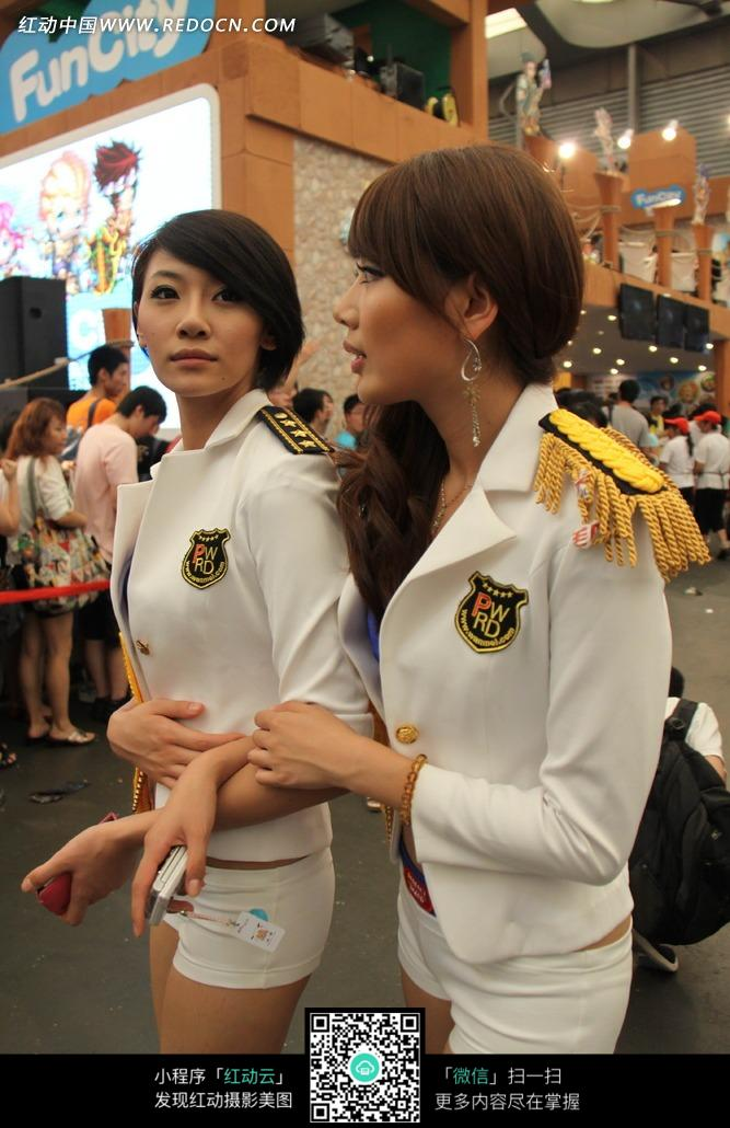 游戏展手牵手白色船长外套的两个超短裤美女图片