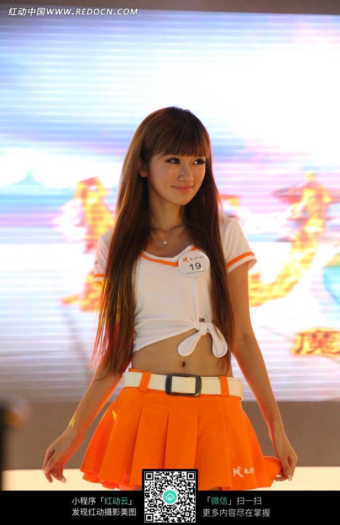 游戏展橙色短裙白色紧身露脐上衣的长发美女图片