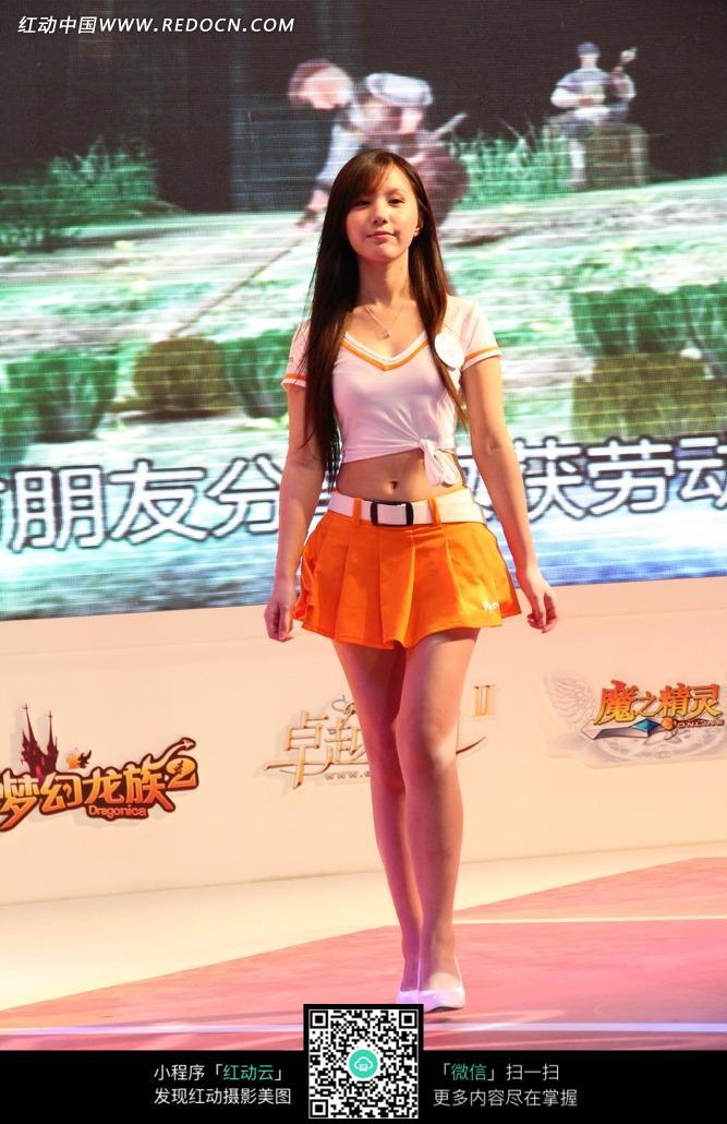 游戏展走秀橙黄色短裙露脐服装的长发美女图片