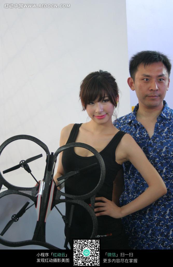 展会模特-拿着黑色游戏道具的美女和男士合影图片