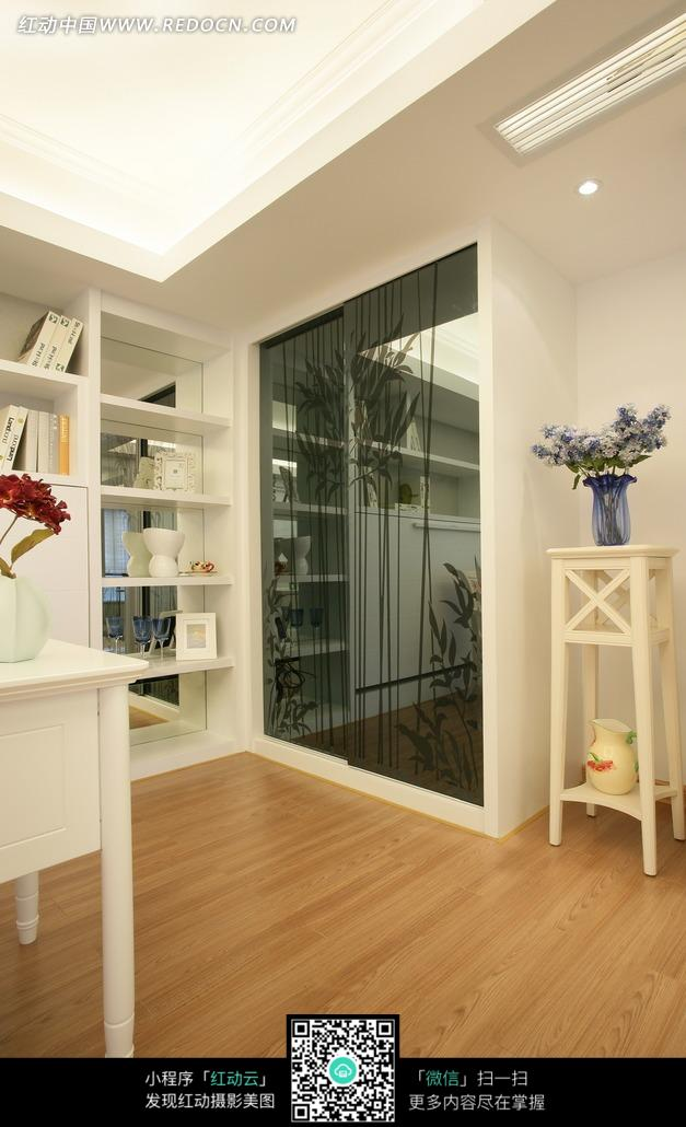 木地板大厅内的玻璃墙壁和白色花架上的紫色花朵图片