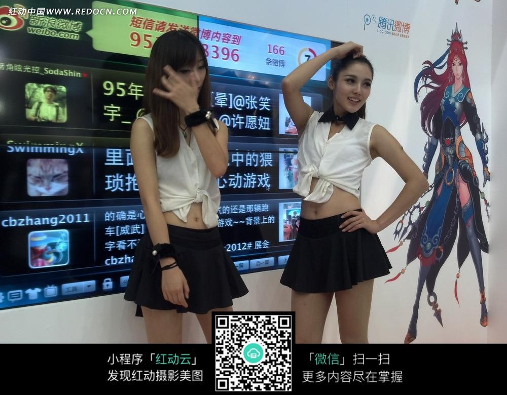 游戏展览会 大屏幕前整理头发摆动姿势的游戏美女图片图片