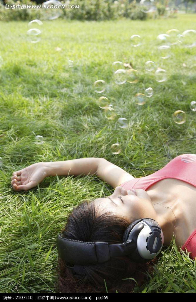躺在草地上戴着耳机听音乐的美女图片