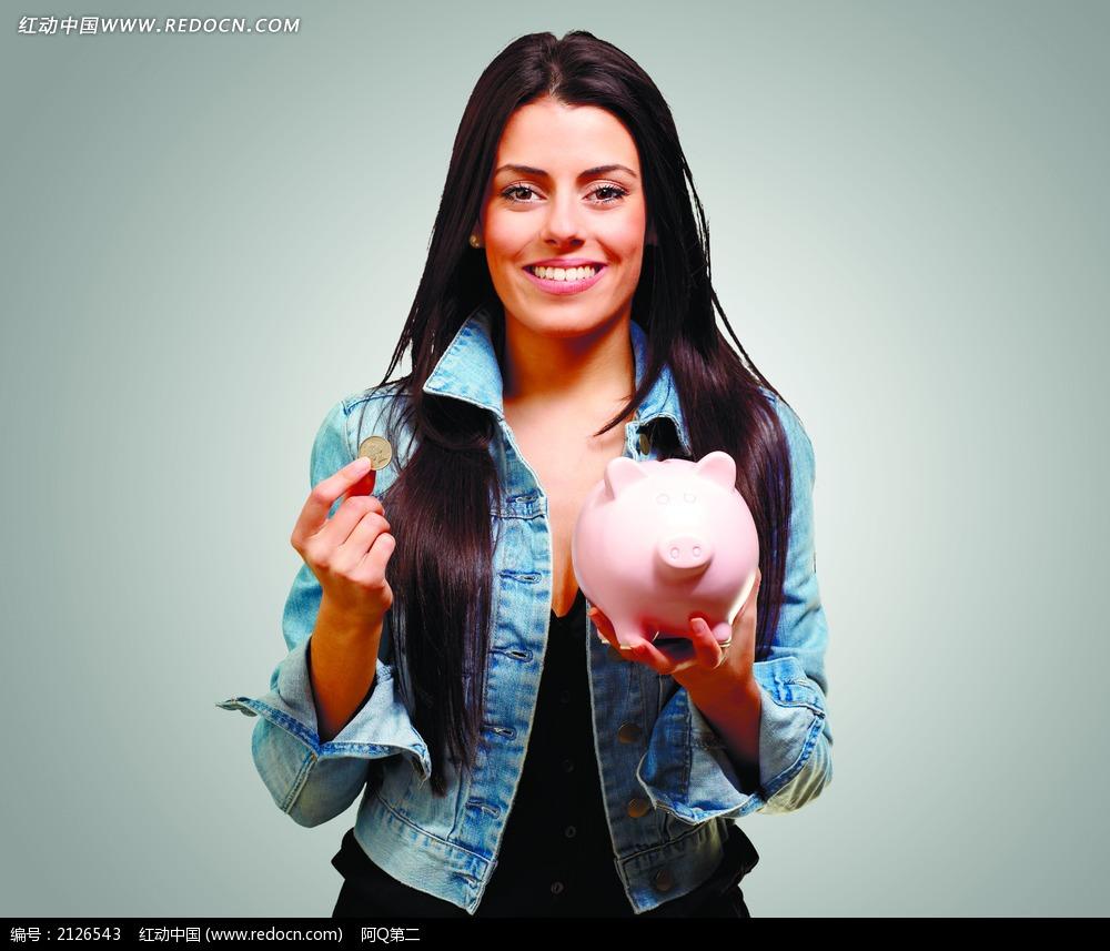 手拿硬币和小猪存钱罐的外国美女图片