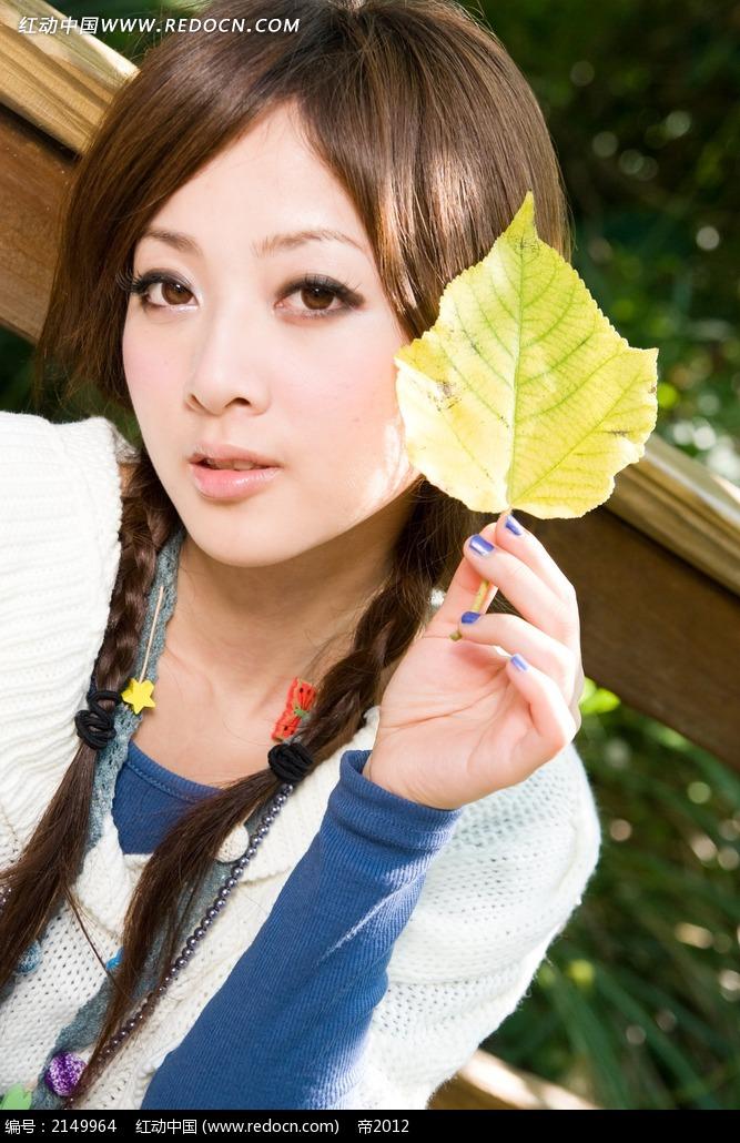 手拿树叶的美女写真摄影图片