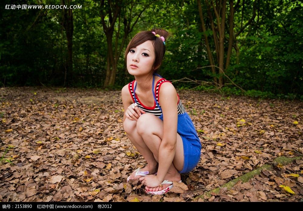 蹲着的美女和落叶写真摄影图片