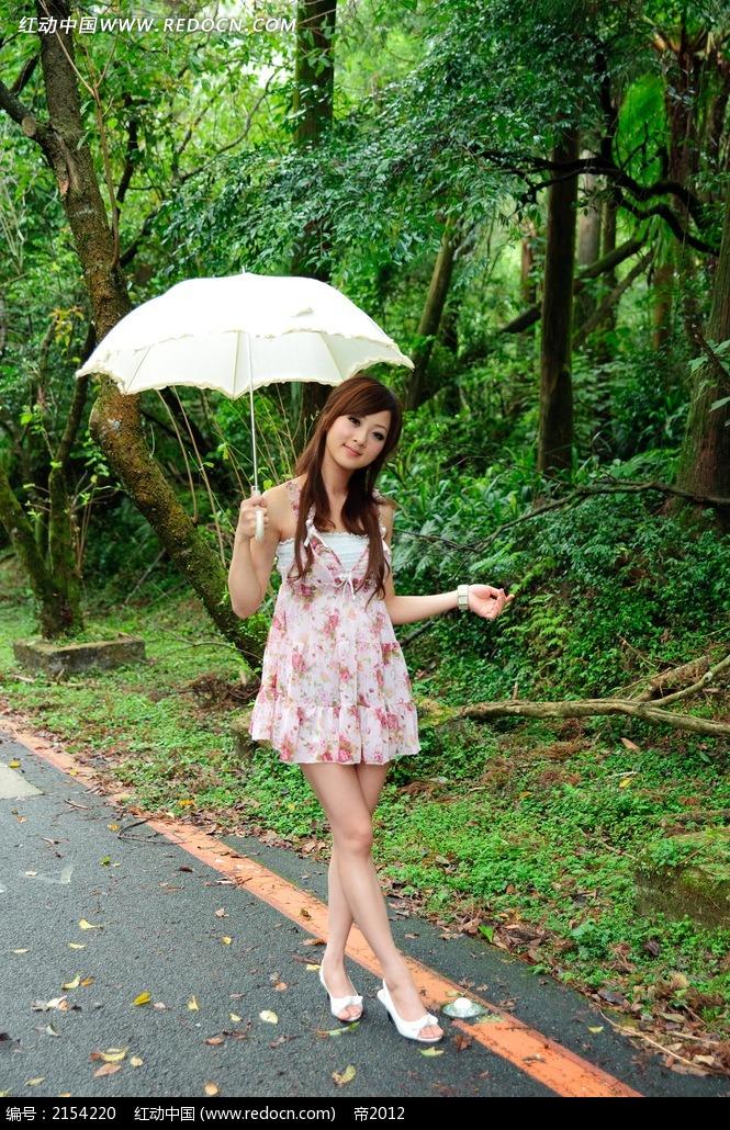 林中撑伞的美女写真摄影图片