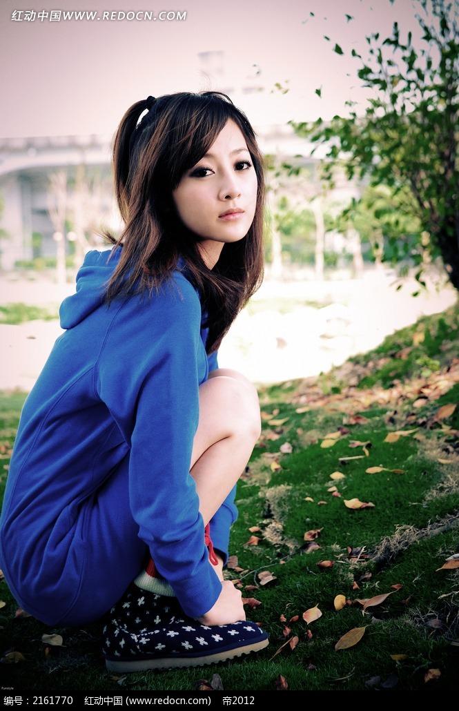蹲着的蓝衣美女写真摄影图片