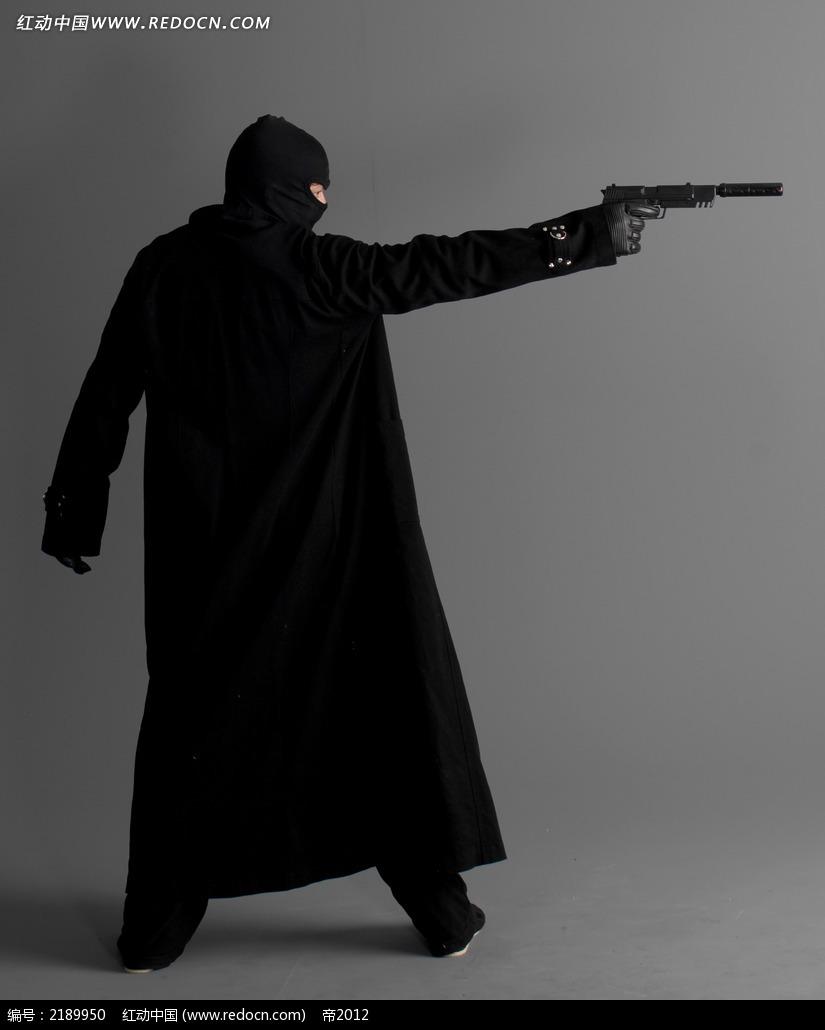 穿黑衣戴头套右手拿枪的男人背影jpg