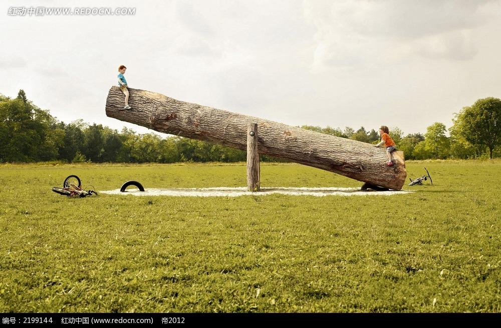 草地上的大木头跷跷板图片