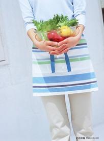 手捧起装有水果蔬菜的玻璃碗