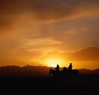夕阳时的骑马人物剪影