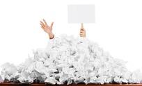 废纸屑纸堆中伸出手举着牌子的人