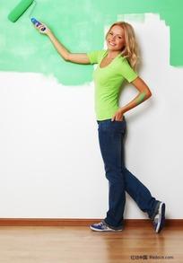 穿牛仔裤刷油漆的女孩