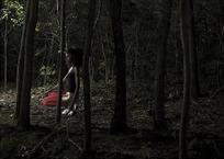 蹲在树林里的女人