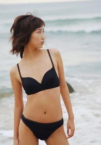 沙滩上挺髋侧望的比基尼美女