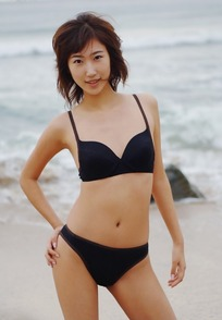 沙滩上挺髋微笑的比基尼美女