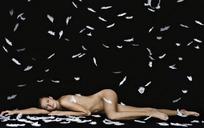 趴在飘落羽毛里的全裸性感美女