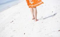 走在沙滩上穿裙女人的脚