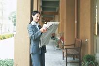 观看报纸新闻的女士照片