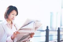 手拿报纸观看的女白领照片
