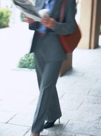 阅读报纸行走的女白领照片