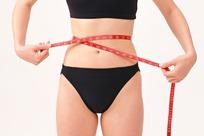 正在用红色软尺测量腰围的女子