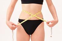 正在用软尺测量腰围的女子