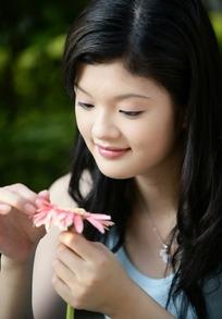 注视粉色非洲菊的女孩