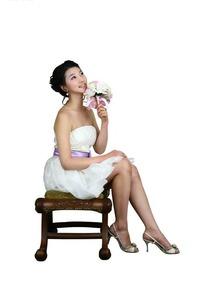 仰着头手拿鲜花头坐在椅子上的美女