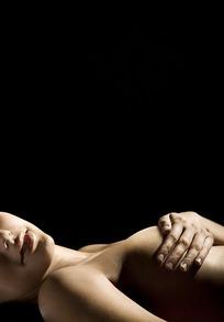 手捂胸部躺下的女模特照片