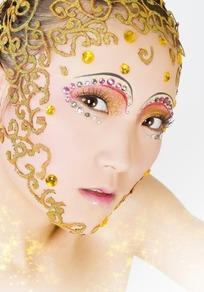 戴着金色花纹头饰眼睛上贴彩色亮片的女子