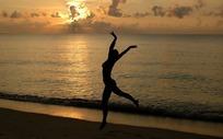 傍晚海滩边做优美跳舞动作的女子