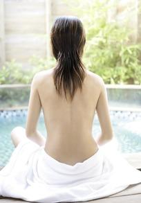 坐在水池边的白色浴巾裹着下半身的女子的背部