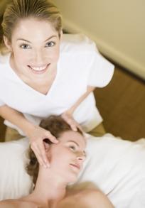 按摩女顾客太阳穴的女美容师抬头微笑图片