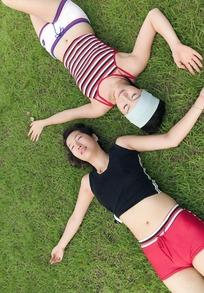 反方向躺在草地上的两个女子