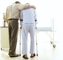 手搭在拄拐杖的老人的肩上的男子