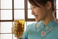 手拿啤酒杯微笑的女孩照片