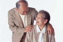 手搭在老奶奶肩膀上弯腰低头对视而笑的老爷爷