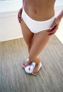 双腿交叉站在体重仪上的女子下半身