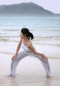 海边双手扶膝半蹲跨步站向右侧身的瑜伽女子图片