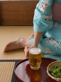 跪坐着的和服女子的脚和拿着啤酒杯的手