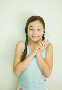 捂着手机听筒表情特高兴的小女孩