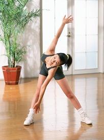 双脚分开身体下压做运动的美少女