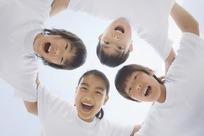 四个搭着肩膀张着嘴的孩子的仰拍
