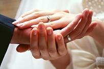 一对恩爱夫妻紧密相连的手的特写