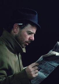 带黑帽子看报纸的外国男人侧面