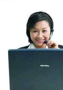 笔记本电脑前微笑的美女客服