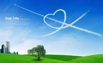 草地上天空中白云组成的一箭穿心图案PSD素材